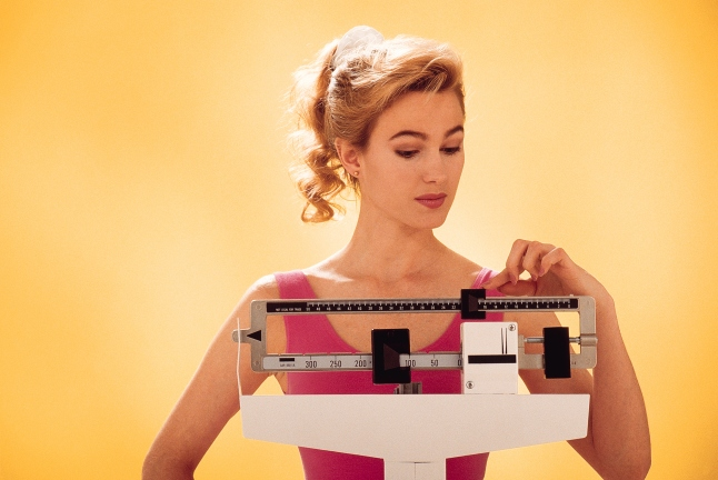 78462057-Woman-weighing-herself-on-scale